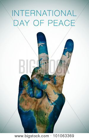 a man hand patterned with an Earth map (furnished by NASA) giving the V sign, as symbol of peace, and the sentence international day of peace