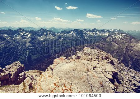 Scenic Overview of Allgau Alps Mountain Range Scenery Stretching into Distance from Rocky Outcrop on Sunny Day with Blue Sky