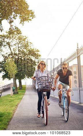 Romantic Couple Cycling Holding Hands