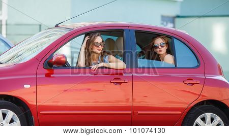 Two happy girlfriends are traveling in the car