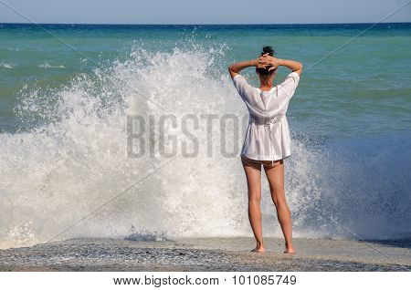 Young woman stands on the sea beach and looks at waves