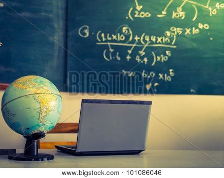 laptop and globe on table of teacher ( Filtered image processed vintage effect. )