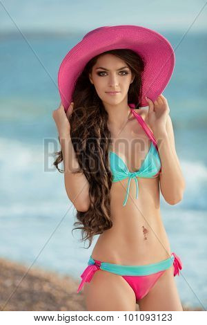 Beautiful Slim Brunette Girl Model Wearing In Fashion Bikini And Pink Hat On The Beach. Summer Outdo