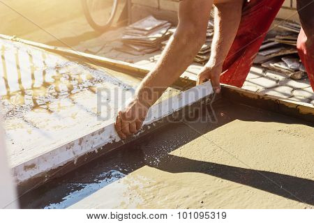 Leveling Wet Concrete Surface With A Metal Screed Board In Evening Sunshine