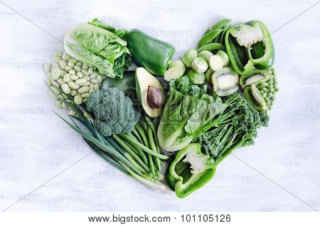 Fresh green vegetables arranged in a heart shape, broccoli, broad beans, capsicum, kiwi, avocado, beans, peas, peppers for healthy living concept