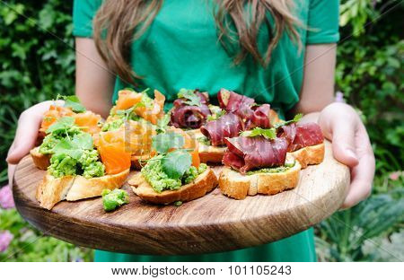 Woman serving platter of small mini bite size canapes, variety of bruschetta