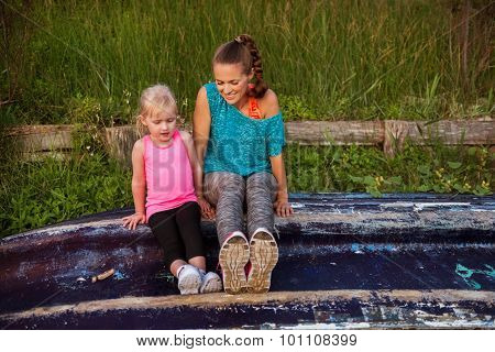 Mother And Daughter Sitting Together On An Upturned Boat
