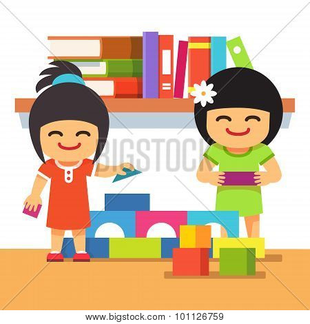 Asian children playing building tower together