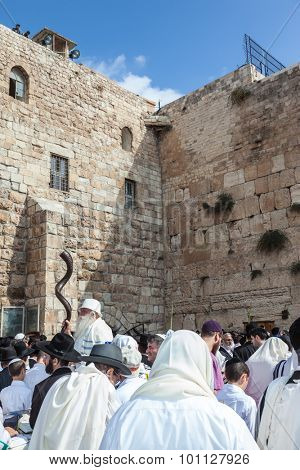 JERUSALEM, ISRAEL - OCTOBER 12, 2014: Crowd of faithful Jews wearing prayer shawls. The area in front of Western Wall of  Temple filled with people. Morning autumn Sukkot