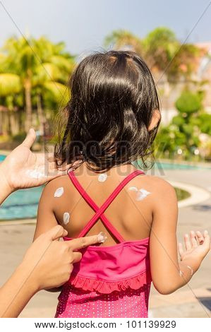 Asian Child with Sunblock Lotion On Her Back Skin Before Swimming