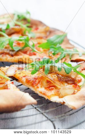 Thin crust pizza slice topped with fresh rocket and caramelised onions
