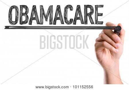 Hand with marker writing the word Obamacare