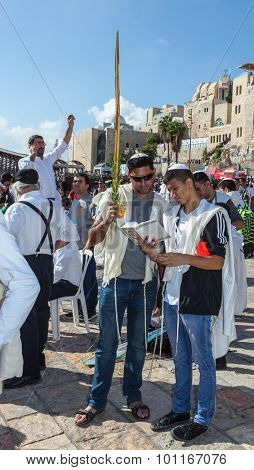 JERUSALEM, ISRAEL - OCTOBER 12, 2014:  Morning autumn Sukkot. The area in front of Western Wall of Temple filled with people. The boys brought the prayer ritual and four plants