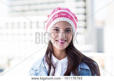 Beautiful woman looking at camera wearing woolly hat outside
