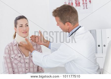 Doctor examining patient wearing neck brace in medical office