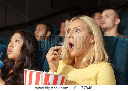 Young woman looking scared while watching a movie