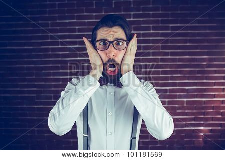 Portrait of shocked hipster against brick wall