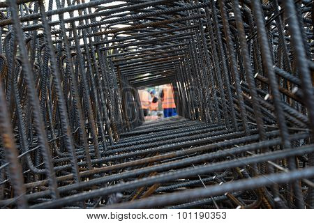 Professional workers seen through steel bars reinforcement on a construction site.