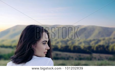 Portrait Of A Girl Looking Afar On The Mountains Background