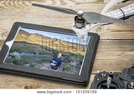 aerial photography concept - reviewing aerial picture of a drone operator on a digital tablet with a drone rotor and radio control transmitter