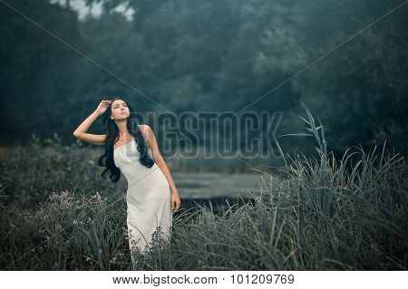 Beautiful but sad woman in fairytale, wood nymph among tall grass and rays of light. Outdoor