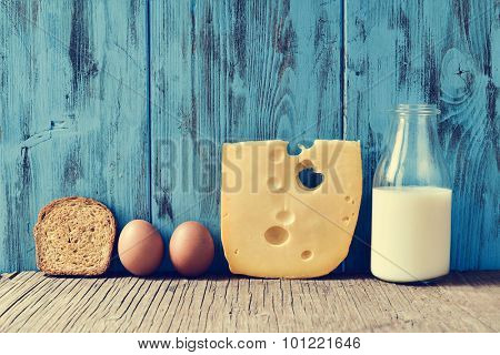 a toast, some eggs, a piece of Swiss cheese and a bottle with milk on a rustic wooden table, against a blue rustic wooden background, with a filter effect