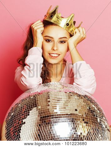 young cute party girl like barbie on pink background with disco ball and crown