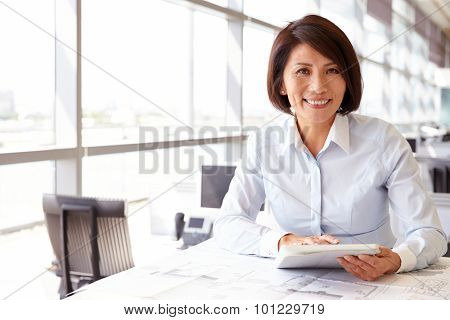 Female architect using tablet computer, looking to camera poster