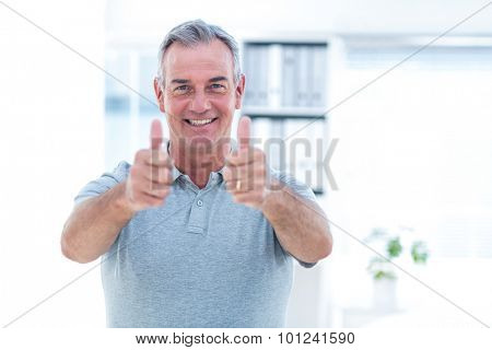 Portrait of happy masseur showing thumps up sign in spa