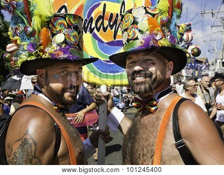 Two men wearing hats walking in the 37th Annual Provincetown Carnival Parade in Provincetown, MA.
