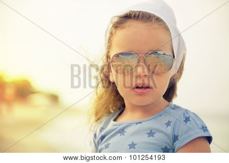 Beautiful little girl with glasses and headscarf on beach.Amazement stares at the camera.Shallow depth of field. Selective focus.