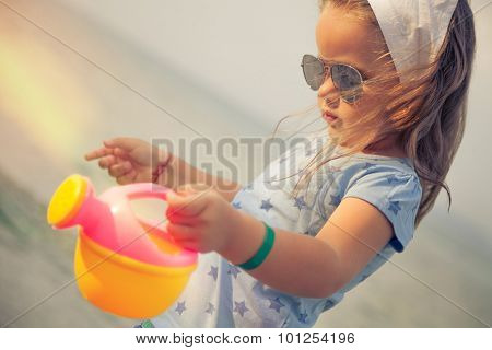 Beautiful little girl with glasses and headscarf on beach.Shallow depth of field. Selective focus.