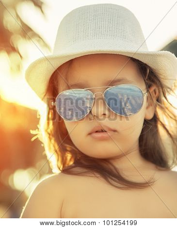 Little girl with glasses and hat on beach, amazement stares at the camera.Shallow depth of field. Selective focus.