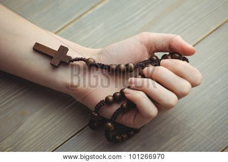 Woman holding wooden rosary beads on table