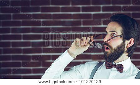 Shocked man holding eyeglases against brick wall poster