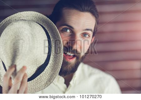 Surprised man holding hat against wall