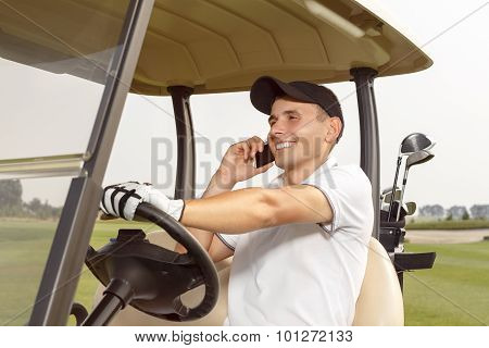 Man sitting in a golf cart and talking on phone