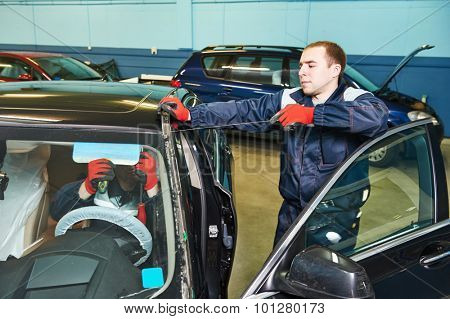 Automobile glazier worker replacing windscreen or windshield of a car in auto service station garage poster