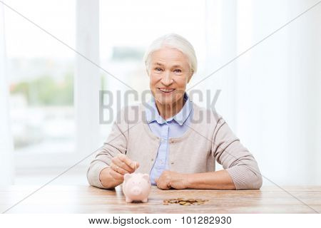 savings, money, annuity insurance, retirement and people concept - smiling senior woman putting coins into piggy bank at home