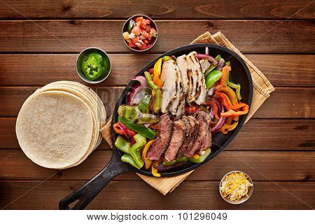 mexican steak and chicken fajitas in cast iron skillet shot top down with corn tortillas poster