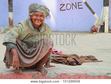old toothless woman is sitting on the pavement