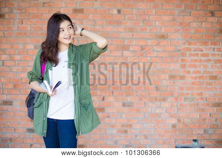 Happy Asian Woman Relaxing Outdoor And Reading Book