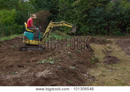 Man Smoothing Terrain With A Mini Digger