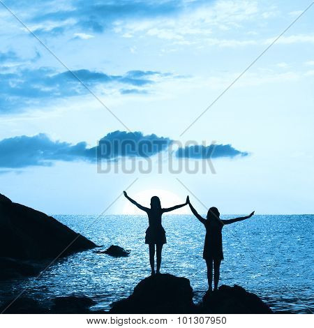 Two Girls Silhouettes At Rocky Beach, Night Scenery