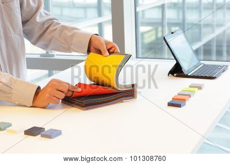 hands looking through color fabric swatches on desk with colored tiles