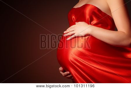 Belly Of Pregnant Woman In  Red Silk Dress Billowing