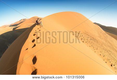 Lonely Man Sitting On Sand At Dune 45 In Sossusvlei - Concept Of Wanderlust In Namibian Desert