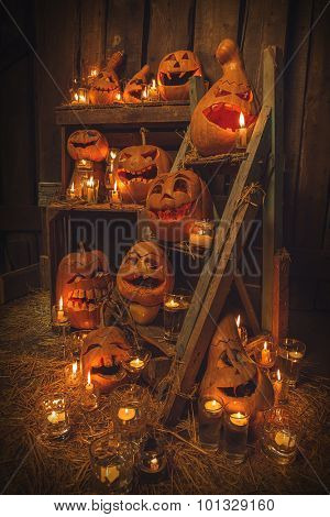 Scary Jack O Lantern halloween pumpkins against wooden wall in darkness