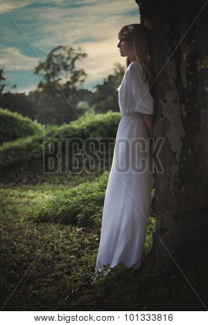 young woman in long white dress lean against big tree looking far away, full body shot, profile, summer day