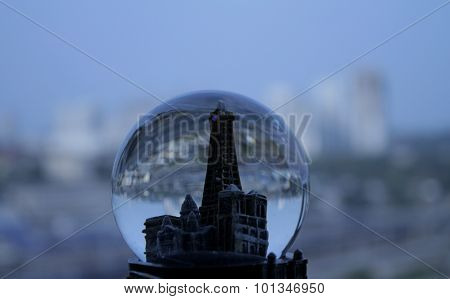 Toy tower in snow glass against real city buildings